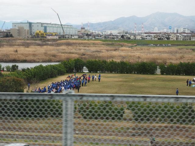 河川敷沿いのグランドで、何かの練習らしきものをしている人たち。