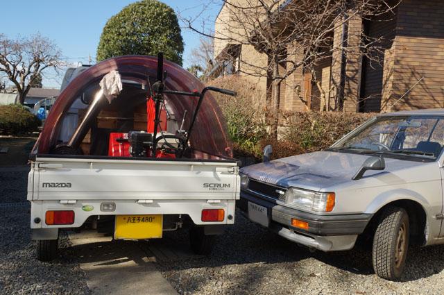 幌馬車みたいになったマツダスクラムに載った分解された機関車焼芋機と除雪機